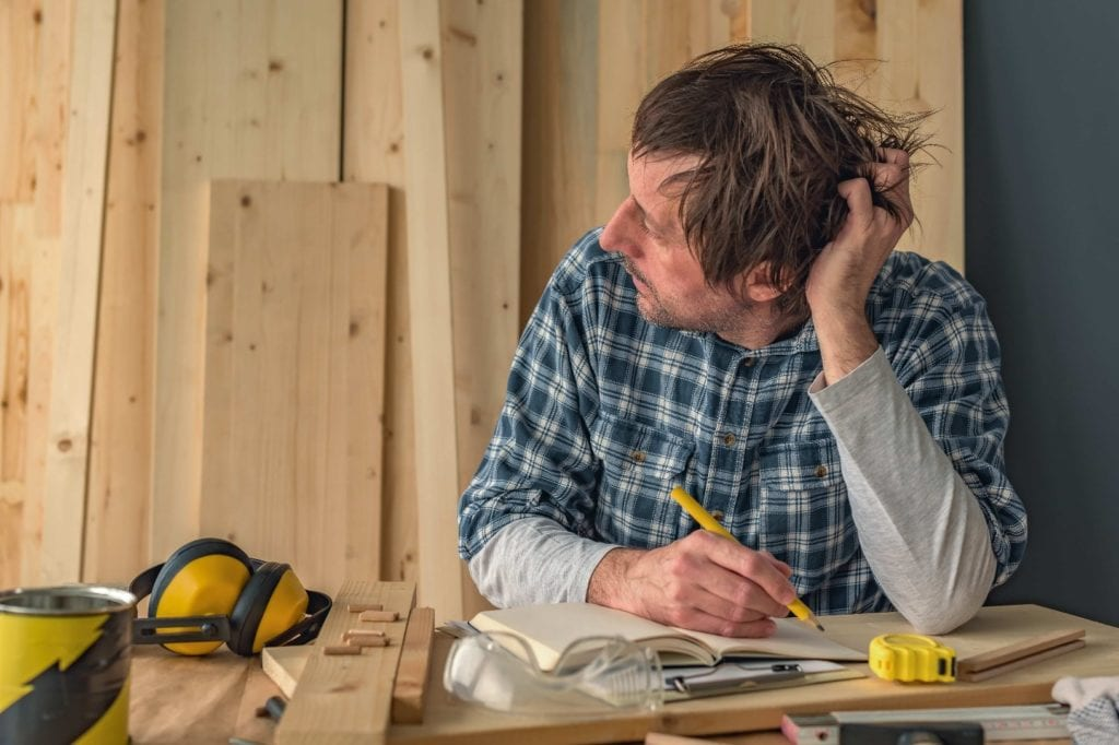 A carpenter contemplating how to fix a mistake.
